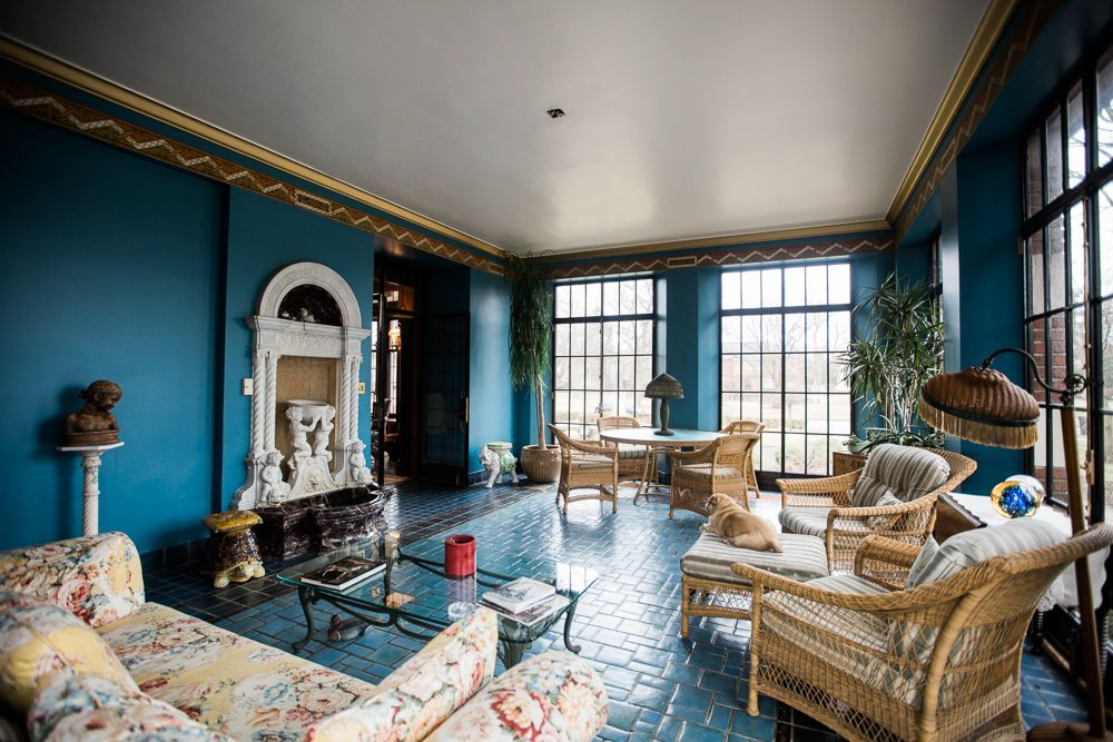 A marine blue solarium with a carved marble fireplace