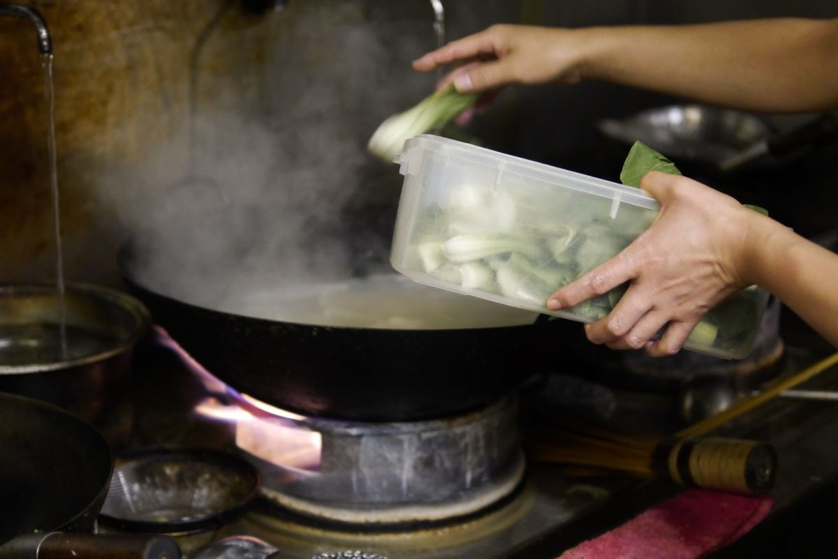 Bok choi being thrown into a wok at Xi'an Impression, a Xi'an Chinese restaurant in north London