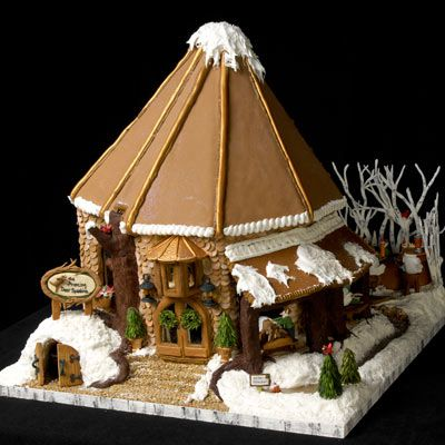 Snow-covered gingerbread cabin and scene.