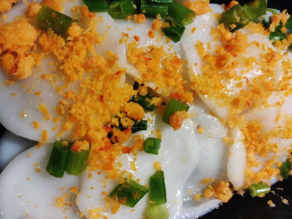 White rice cakes stacked on top of one another and topped with dried, ground shrimp and green onions
