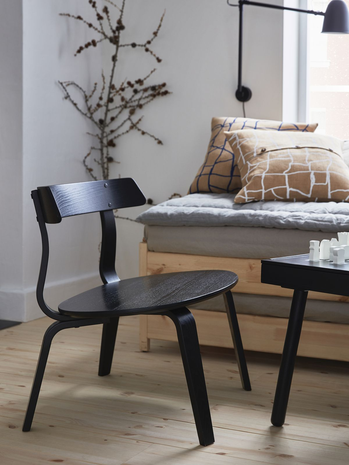 A black armchair with a curved back and round seat sits in front of a bench with brown accent pillows.