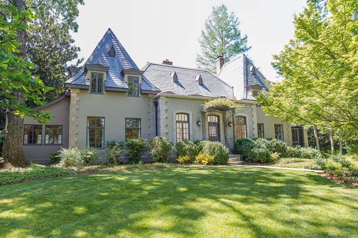 Gray European home with large front yard.