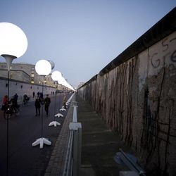 """People pass by balloons of the art project """"Lichtgrenze 2014"""" or lightborder 2014, along the Berlin Wall in Berlin, Germany, Friday, Nov. 7, 2014. The light installation featuring 8,000 luminous white balloons commemorates the division of Berlin, marking the 25th anniversary of the fall of the wall on the weekend."""