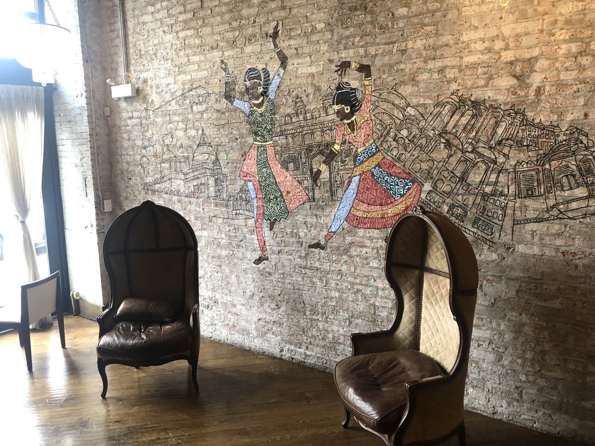A brick wall with a mural and two chairs.
