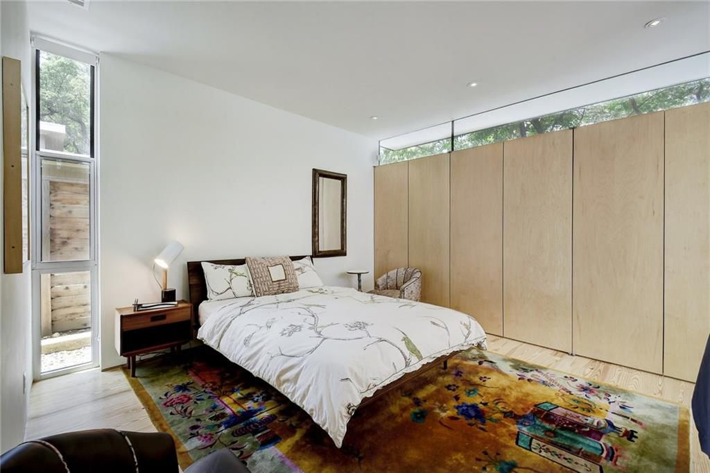 A modern bedroom with a wall of closet-type doors/cabinet that stops just short of the ceiling, where there is a window the length of the wall. A bed with a simple frame and two nightstands are against the adjacent wall, on top of a rug. on the left side of the wall is a stack of windows that creates a vertical column.