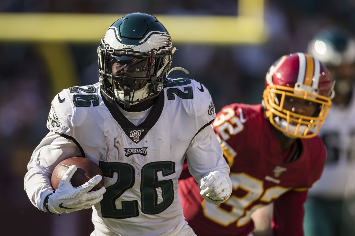 Miles Sanders of the Philadelphia Eagles carries the ball as Jimmy Moreland of the Washington Redskins defends during the first half at FedExField on December 15, 2019 in Land