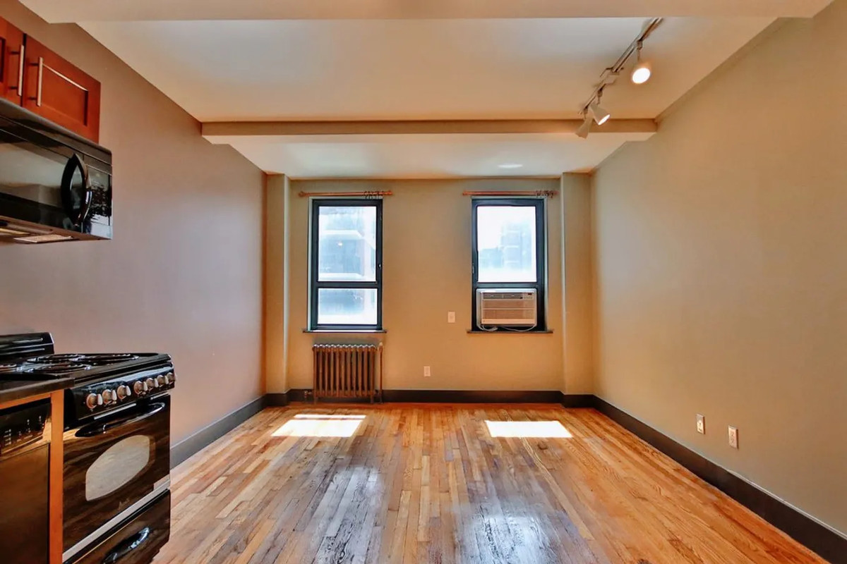 A living area with hardwood floors, two windows, and beamed ceilings.