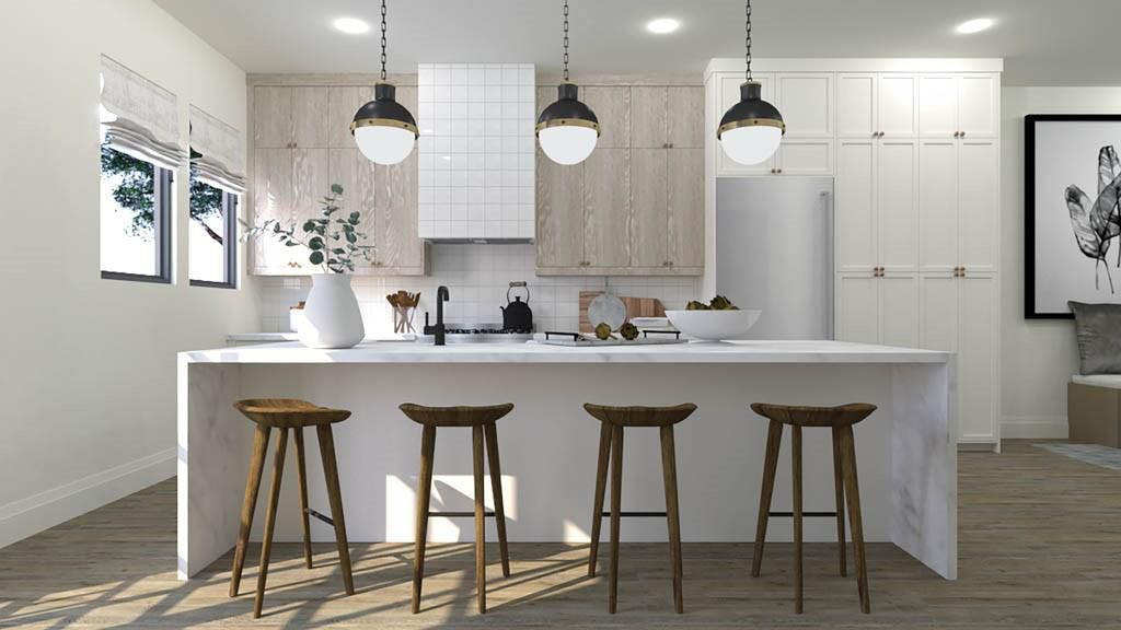 A waterfall countertop and stools and mixed cabinetry in a kitchen.
