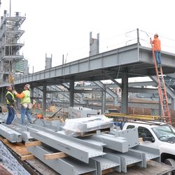 Steel being lifted off a trailer truck, on Waveland -