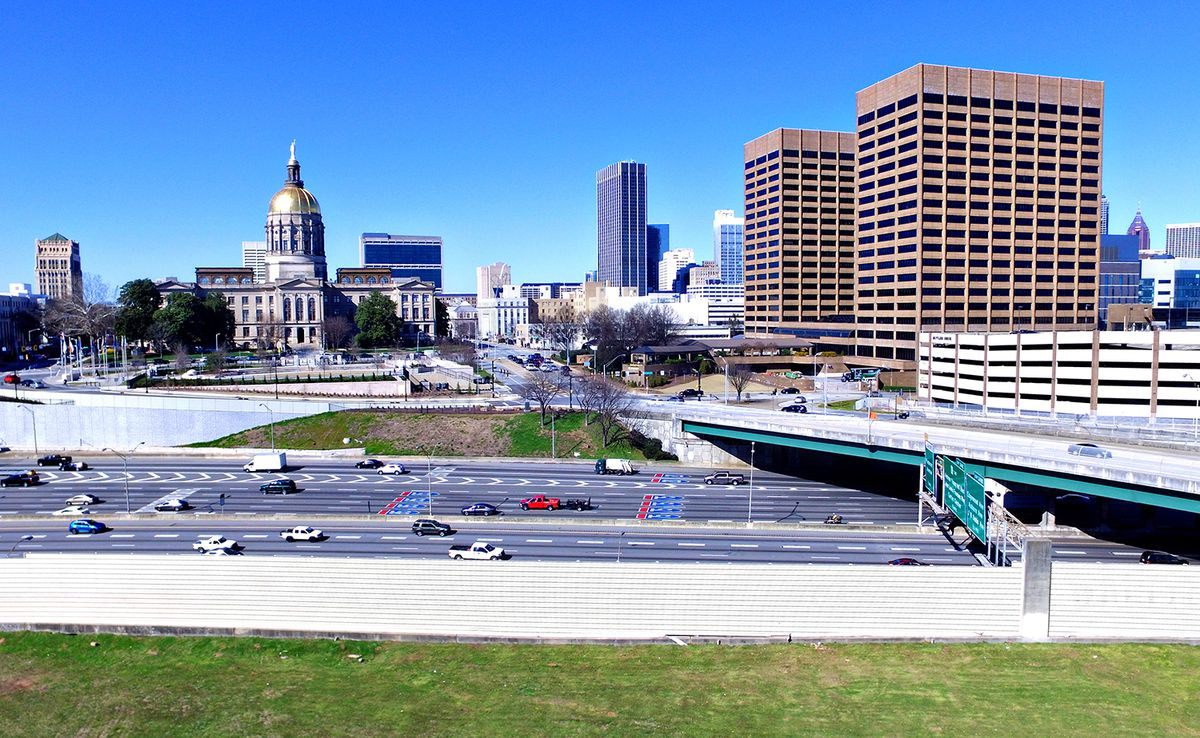 A photo of a large Atlanta highway with a gold dome capitol building in the distance.