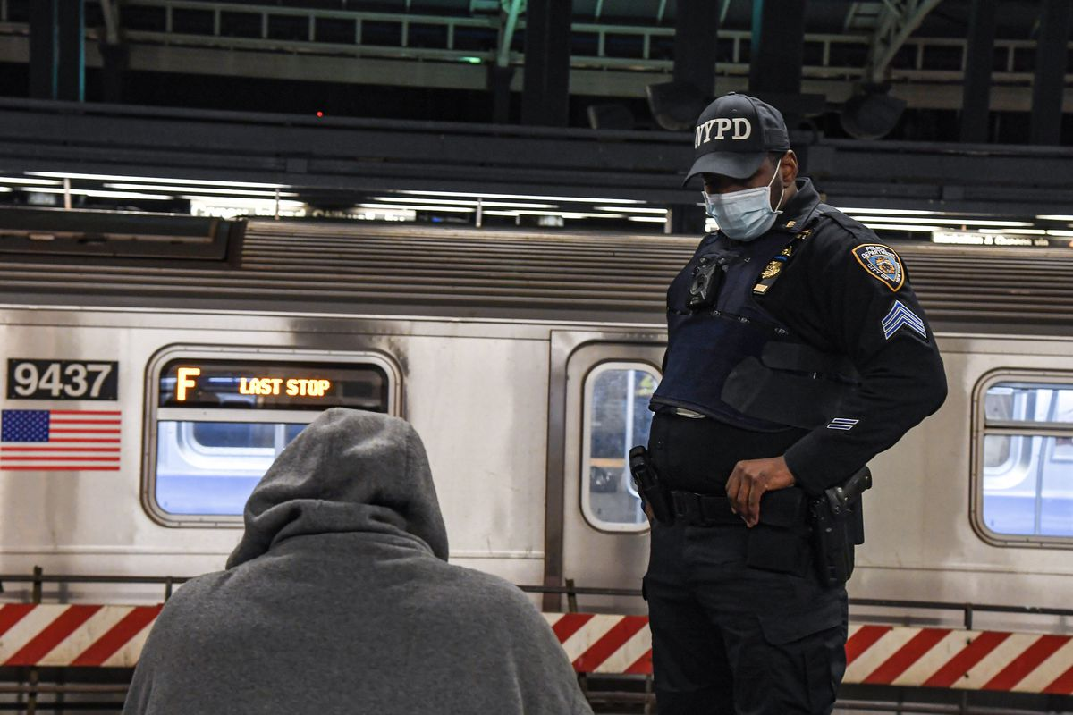 An individual sits on a bench in a subway station, a train is in the background, and an NYPD officer with a face mask looks over him.