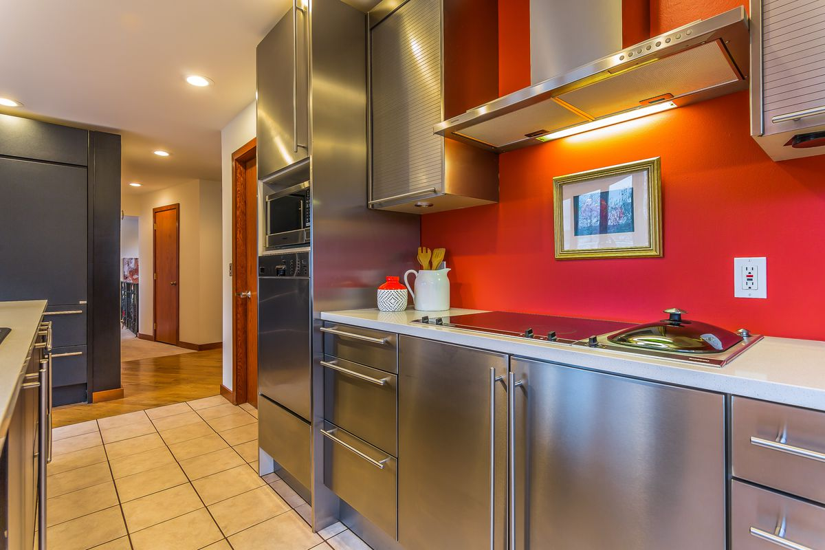 A kitchen with chrome cabinets and hardware and a red accent wall