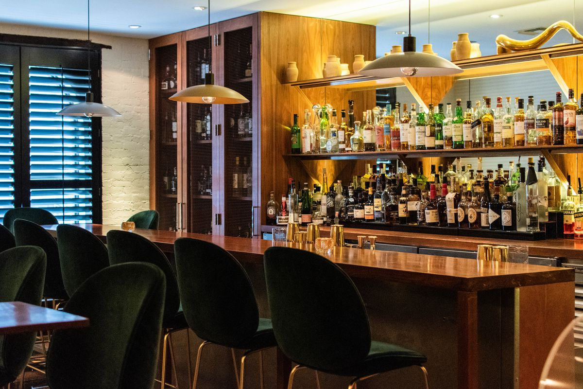 A wooden bar with stools on one side and a shelves featuring several bottles of liquor on the other side.