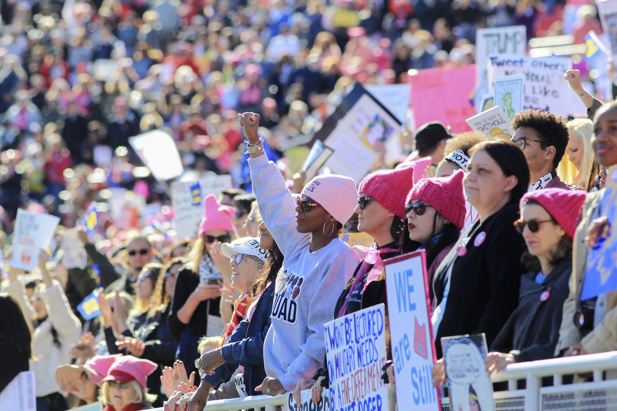 """Attendees at the Women's March """"Power to the Polls"""" launch event, some wearing pink """"pussy hats and carrying signs, one in the center of the photo with a raised fist."""