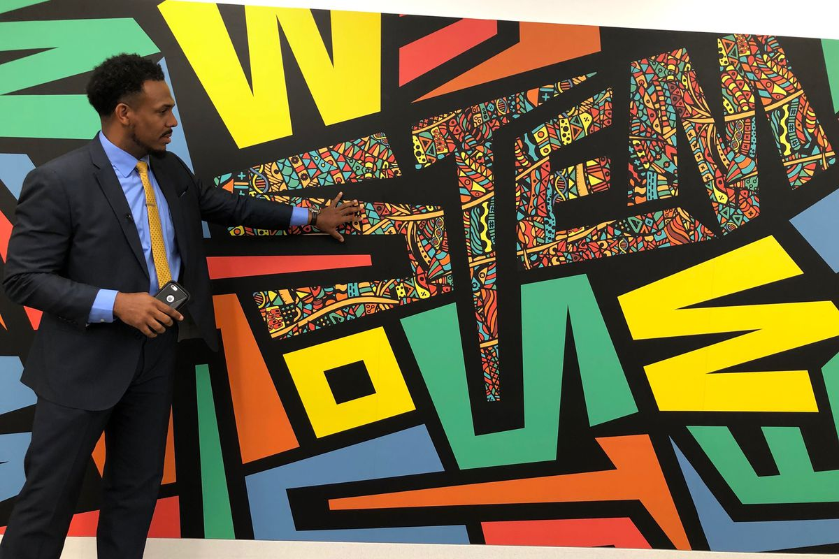Principal Conrad Timbers-Ausar stands in front of a mural at the new Englewood STEM high school.