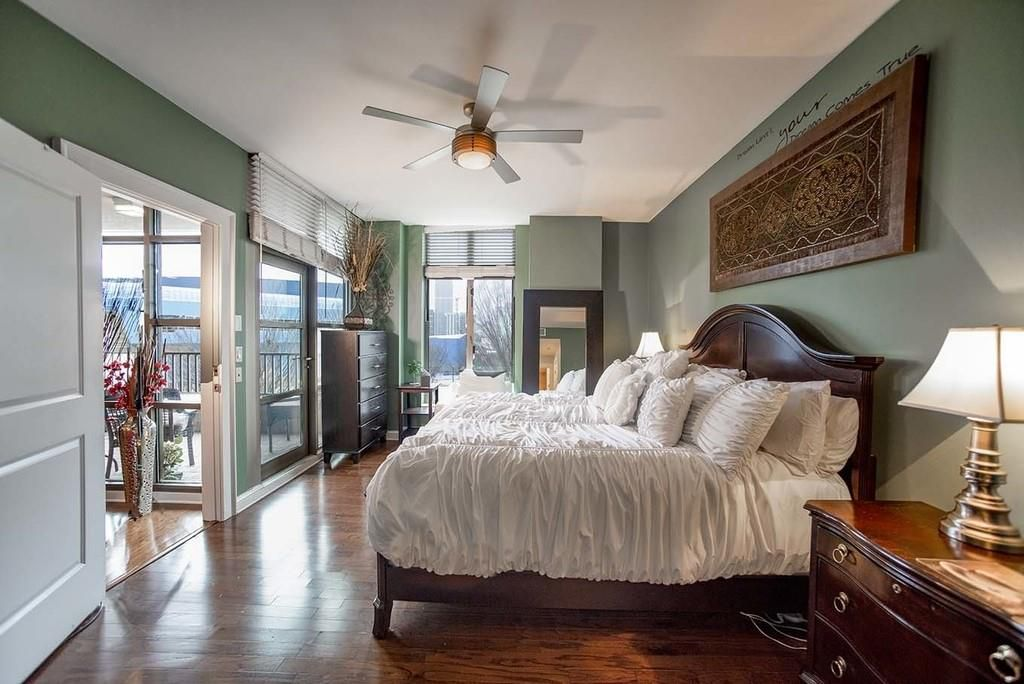 Bedroom with king bed, nightstands and lamps, and wall art above the bed.