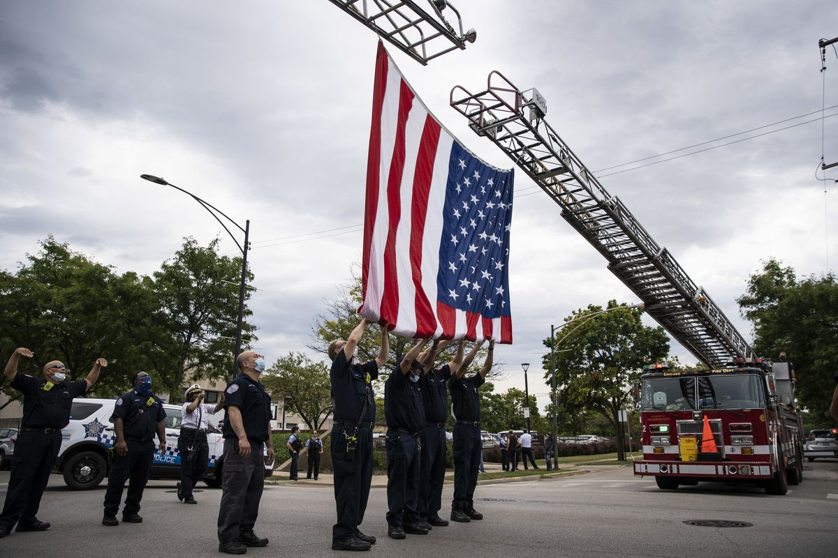 Chicago Fire Department personnel take down the American flag outside the Cook County medical examiner's office after the procession for CPD Deputy Chief Dion Boyd, who was found dead in his office Tuesday morning, July 28, 2020 of an apparent suicide.