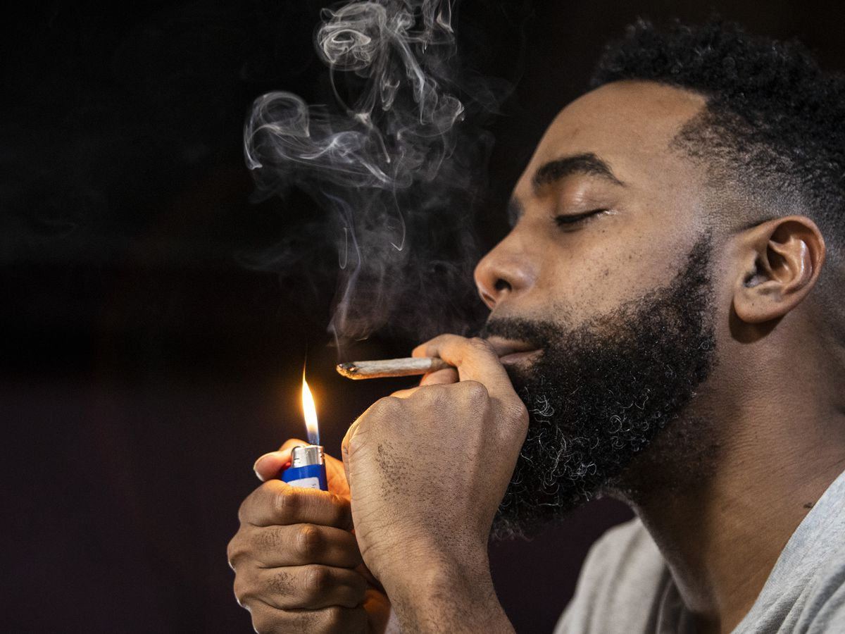 Cannabis consultant Mike Malcolm smokes a joint in a North Side home as he explains what customers can expect at dispensaries now that recreational marijuana is legal in Illinois, Jan. 8, 2020.
