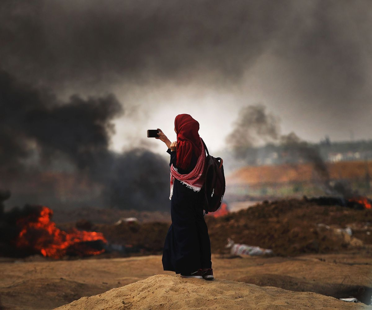A Palestinian woman documents the situation at the border fence with Israel as mass demonstrations continue on May 14, 2018 in Gaza City, Gaza.