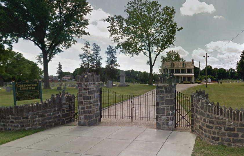 The entryway to the Greenwood Knights of Pythias Cemetery. There is a stone fence. Behind the fence is land. In the distance is a building.