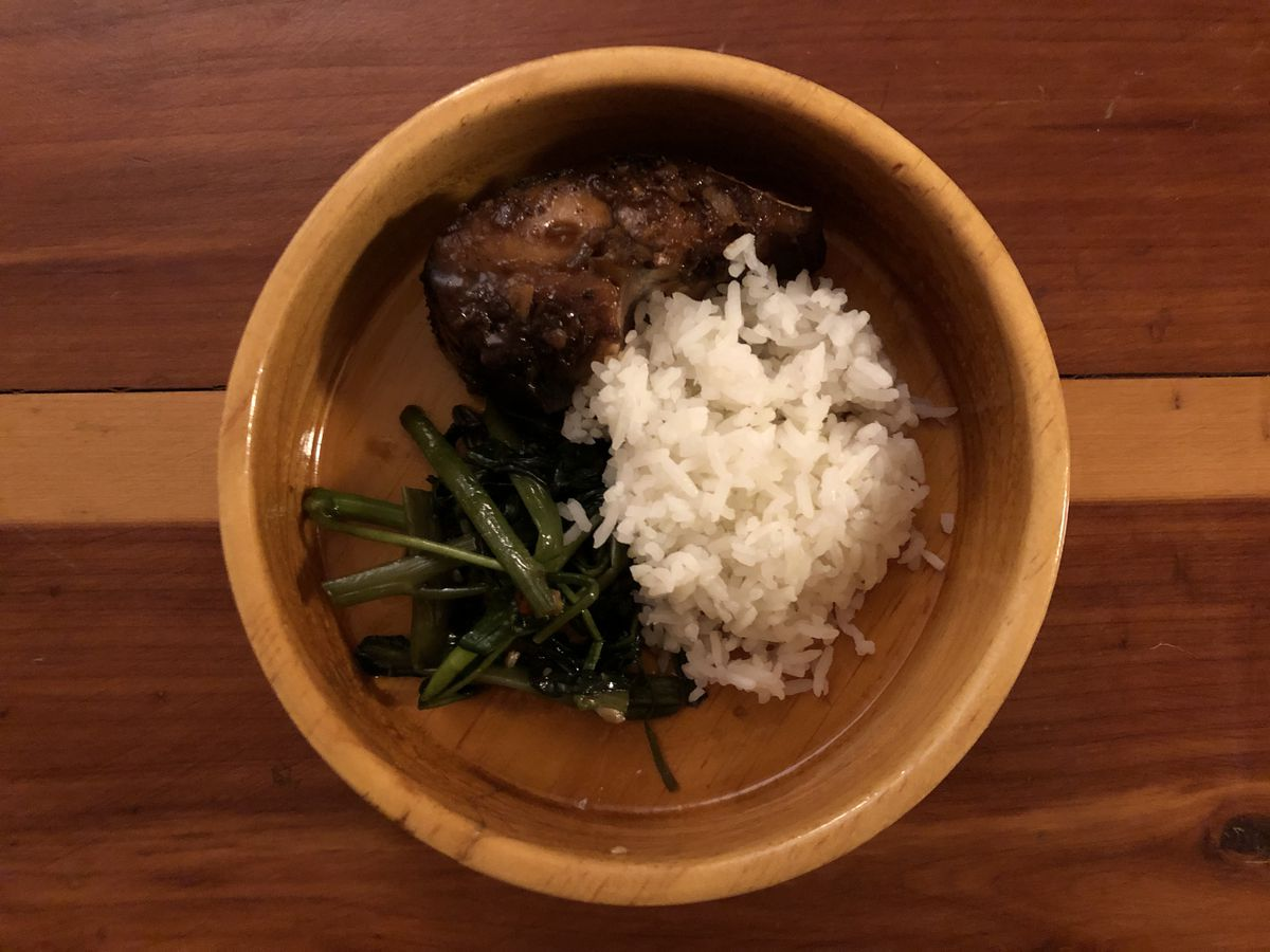 A light wooden bowl with dark fish, cooked greens, and white rice set on a reddish brown wooden table