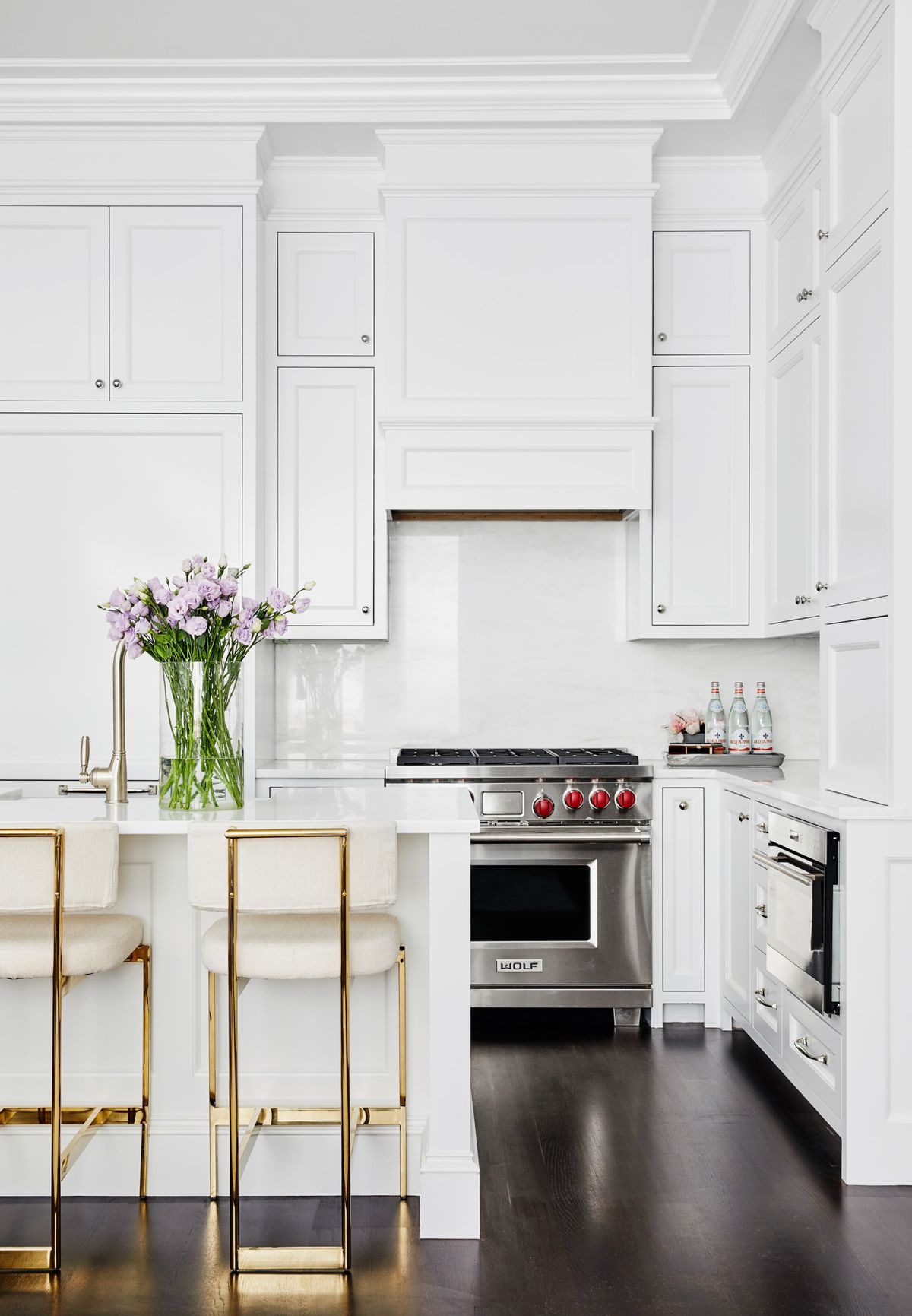 A clean, all-white kitchen with ample built in cabinets. The kitchen is accented by two gold metal-framed chairs that are tucked neatly under the kitchen island. There is a large bouquet of freshly-cut flowers sitting on the island.