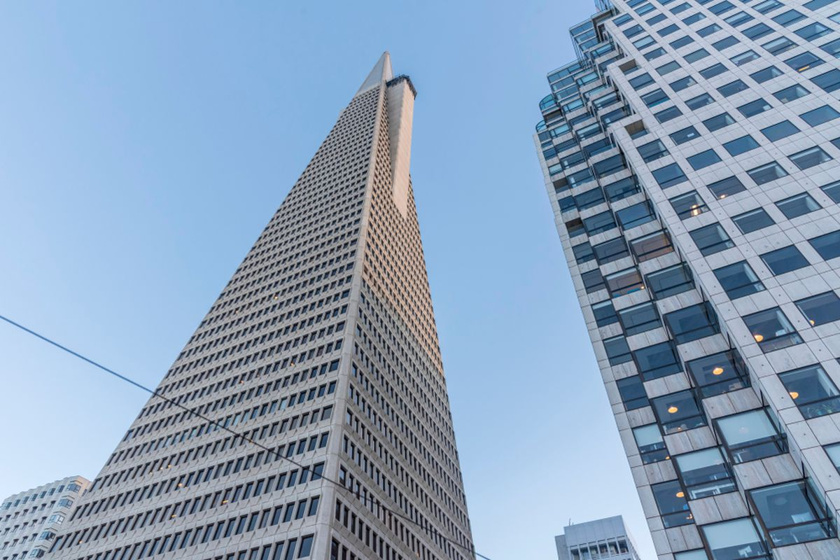 An extremely low-angle photo of a triangular high-rise.