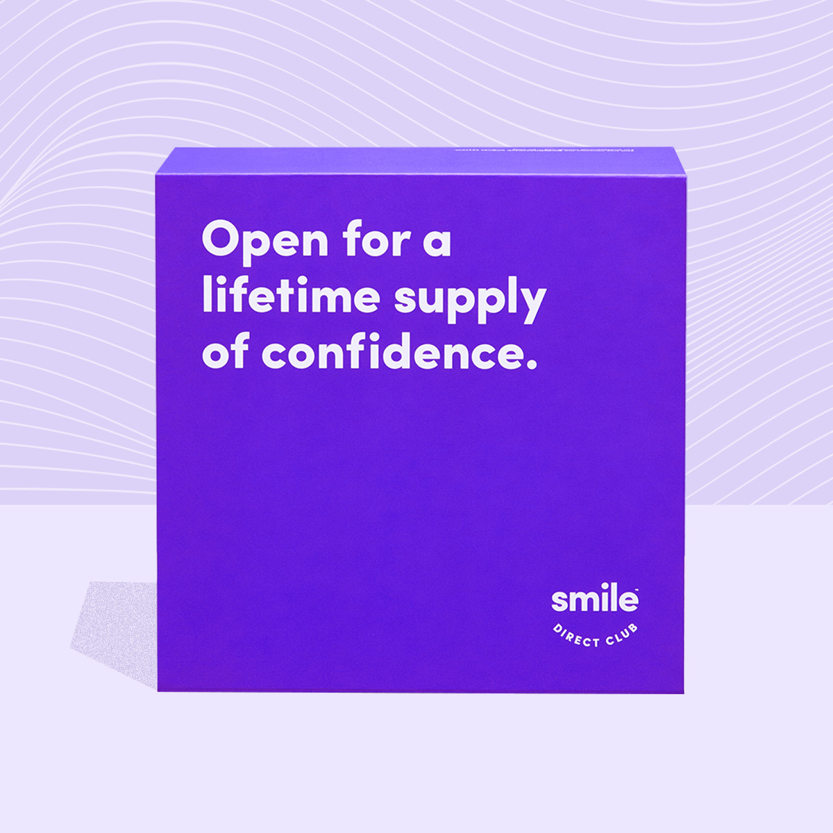 """A purple box from Smile Direct Club that says """"Open for a lifetime supply of confidence,"""" with aligners inside."""