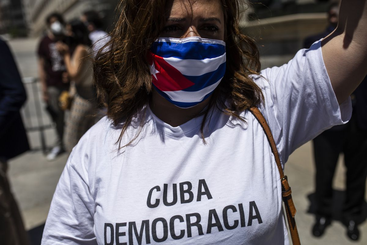 """A protester wearing a Cuban-flag mask and a T-shirt that reads """"Cuba democracia."""""""