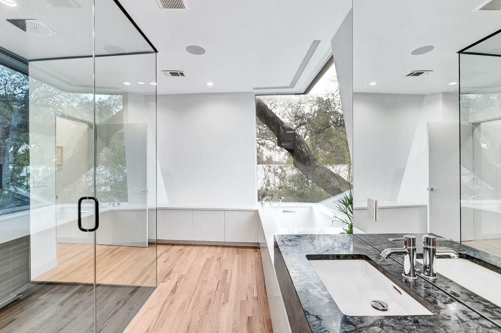 A photo of a bathroom with wood floors, a soaking tub in the corner with a tree just outside of it, a sink with a marble surround, and a glass-enclosed shower.