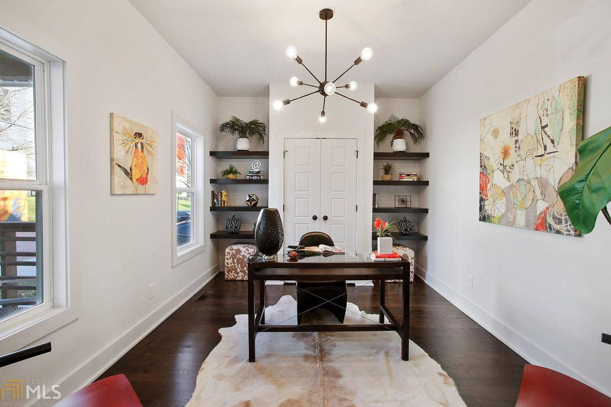 Room with desk and chair, area rug, and built-in shelves holding collectibles.
