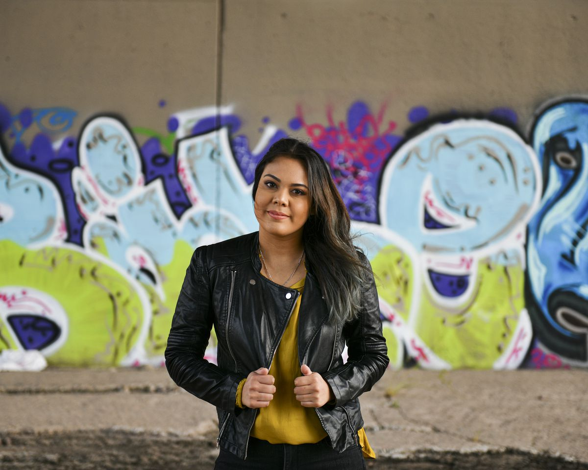 """Alvarez smiles slightly in a black leather jacket and mustard colored blouse. She stands in front of blue, green, and purple wildstyle graffiti, the letters """"B"""" and """"e"""" visible on either side of her."""