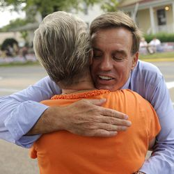 Sen. Mark Warner hugs Mary Harrison while he walks in the parade during the Labor Day parade in Buena Vista, Va. on Monday, Sept. 3, 2012. The parade is the first big political event of the season in the Shenandoah Valley.