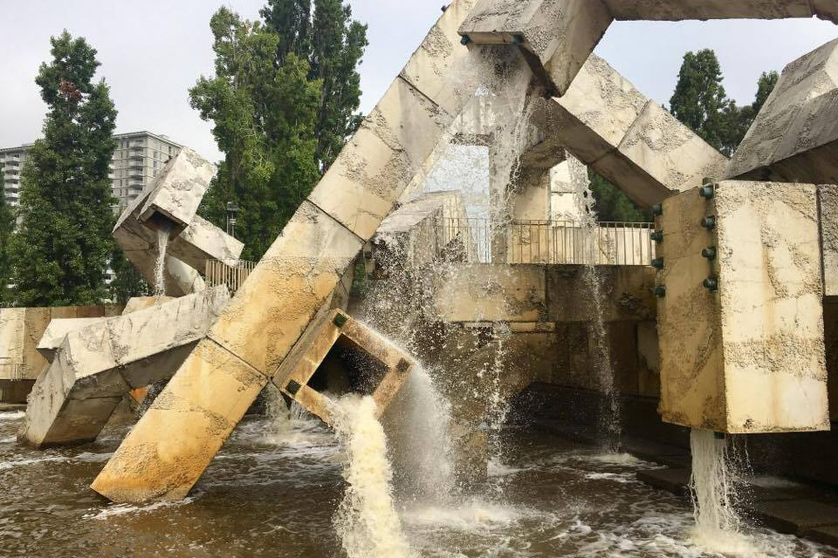 Brutalist fountain, boxy, concrete, running with water.