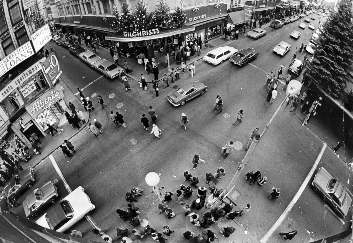 Aerial view of a busy intersection, with cars and pedestrians, in the early 1970s.