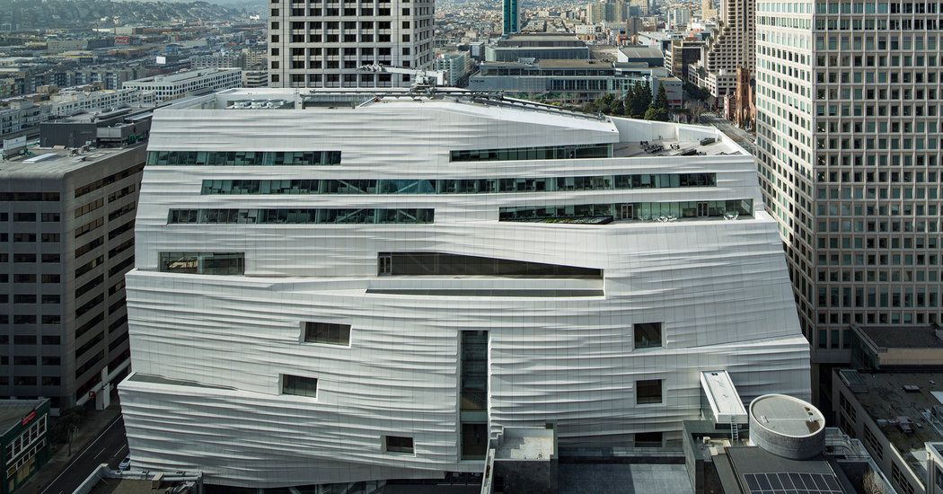 The exterior of San Francisco Museum of Modern Art. The facade is white and contoured with many windows.