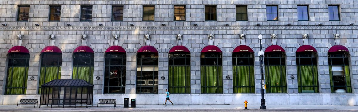 A jogger runs along an empty sidewalk in front of the Hotel Monaco in downtown Salt Lake City during the COVID-19 pandemic on Monday, April 13, 2020.