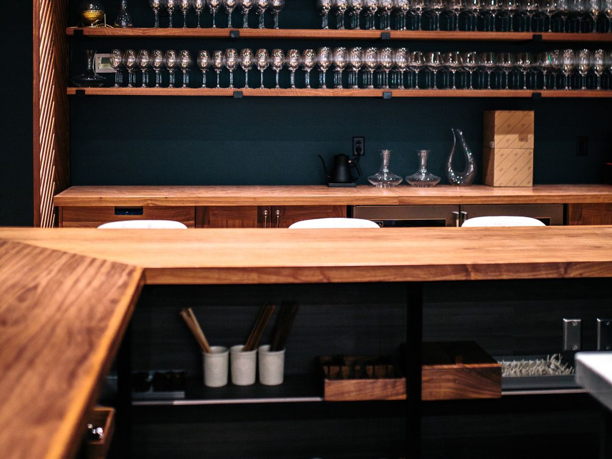 A dark dining room bar that's filled with still wood shelves with small porcelain serving implements