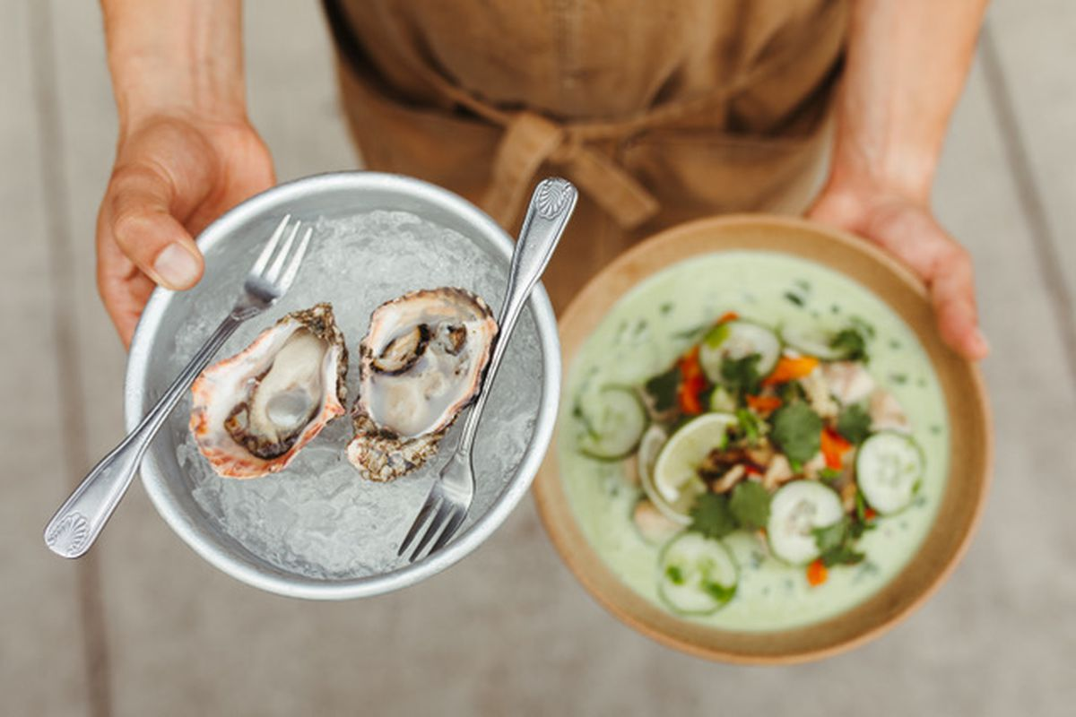 A man holds two plates: One platter of oysters with seafood forks, and a fish dish with cucumbers, lime, and cilantro.