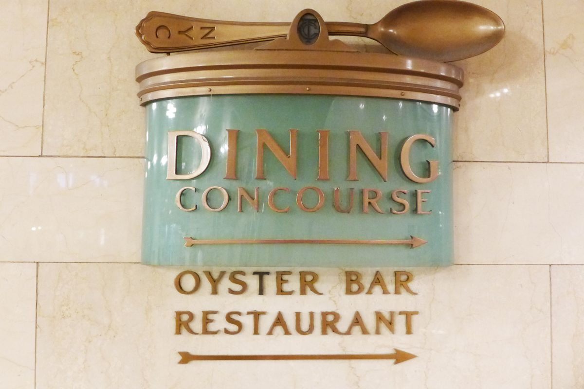 A 3D sign in the hallway includes a gigantic brass chowder spoon and an arrow pointing toward the Oyster Bar...
