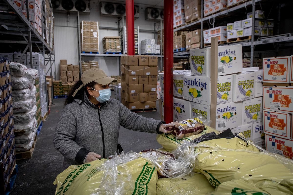 A street vendor inspects potatoes in a warehouse