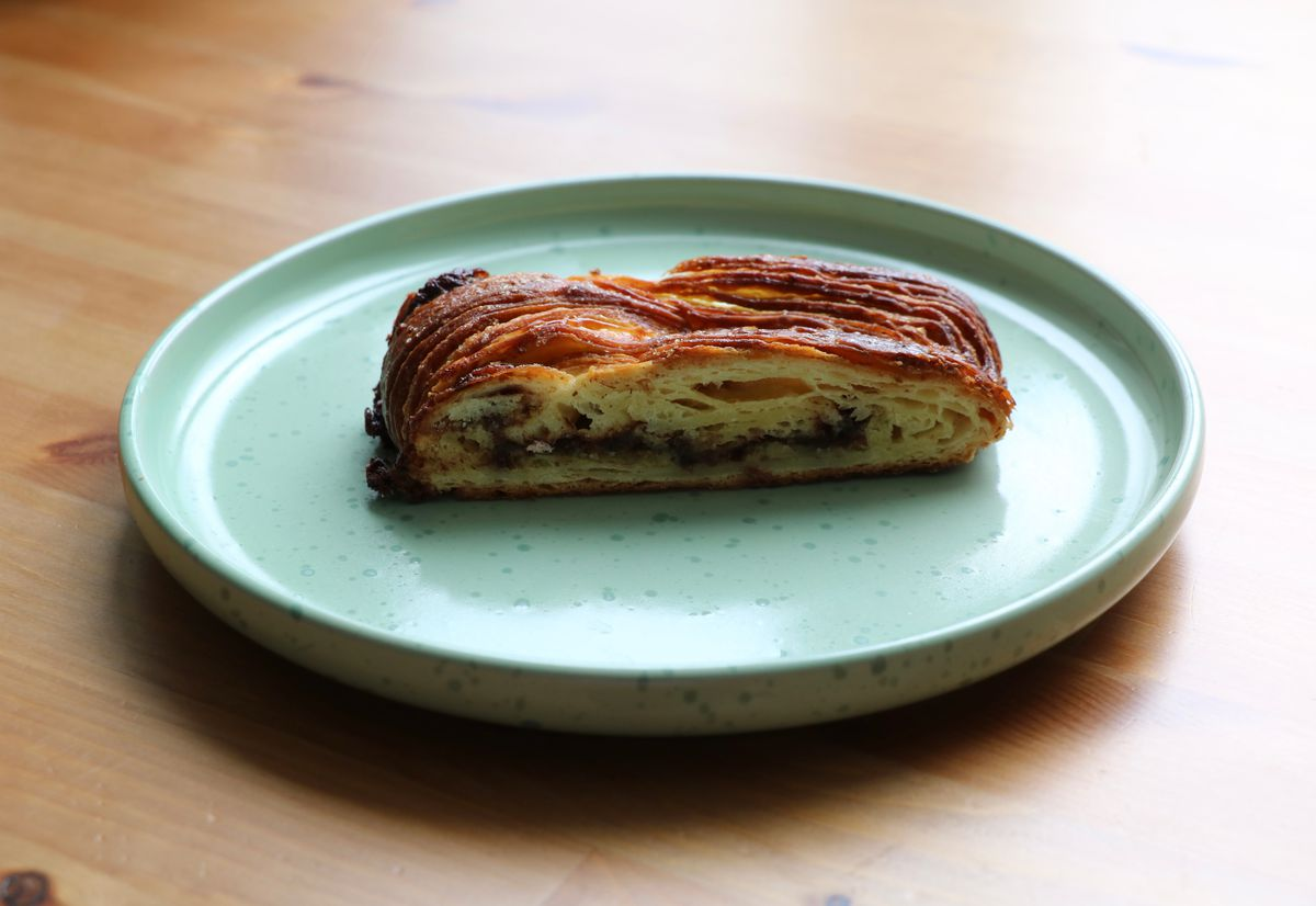 A slice of chocolate marzipan babka on a light green plate on a light wooden table