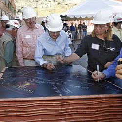 From left, Zeke Dumke Jr., Kaye Dumke and Kari Astle sign a commemorative poster that will travel with copper during fabrication.