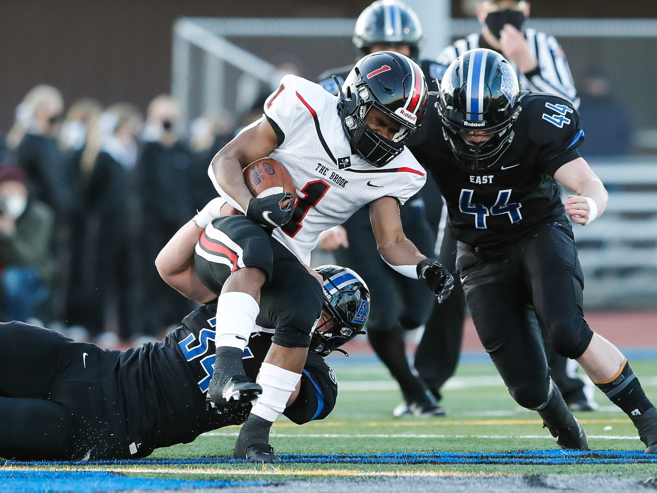 Lincoln-Way East's Jack Hawkinson (34) and Ben Kingsbury (44) take down Bollingbrook's Jaquan Howard (1).