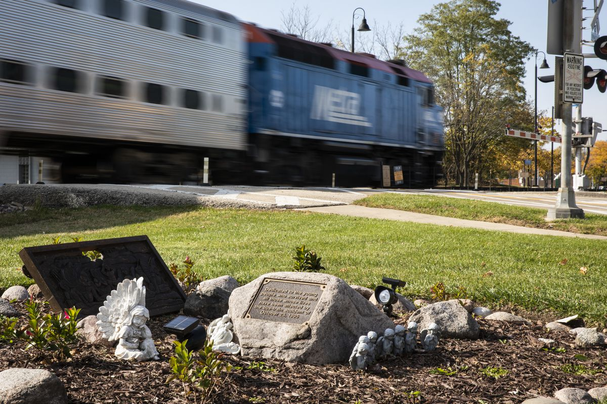An outbound Metra train travels past a memorial at Algonquin Road and Northwest Highway in Fox River Grove. At the same location on Oct. 25, 1995, inbound Metra train No. 624 crashed into a school bus, killing seven teenagers on their way to class at Cary-Grove High School and injuring the bus driver and 24 passengers.