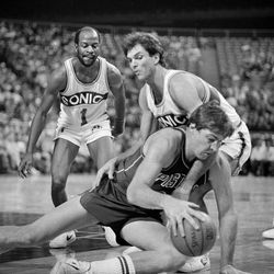 Bill Laimbeer (dark shirt) of the Detroit Pistons, and Danny Vranes, right, Seattle Sonic, tangle and fall to the floor after a loose ball in the second quarter of their game in Seattle, Dec. 11, 1983. Laimbeer was called for traveling. Gus Williams (1), Sonic, watches in the background.