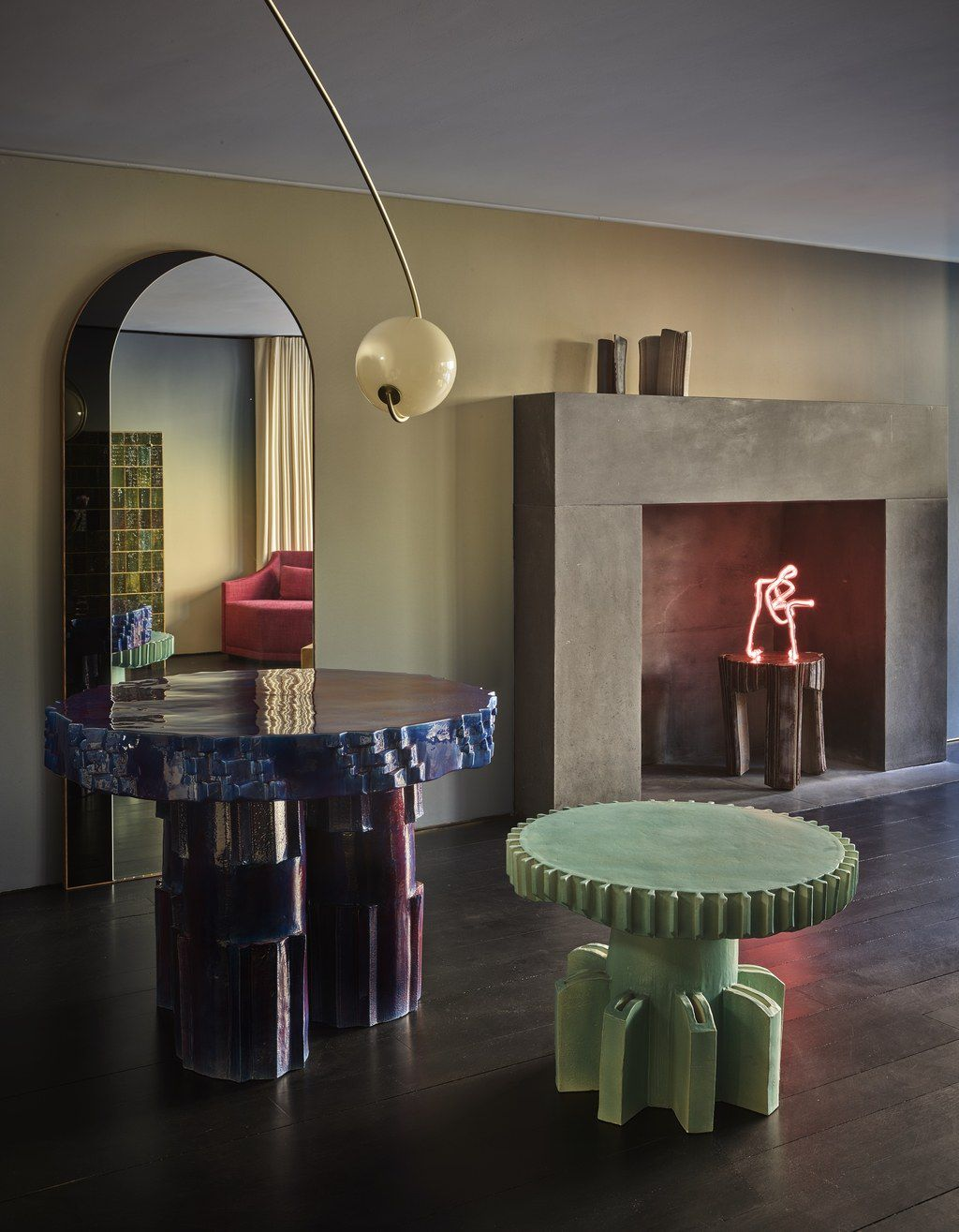 A living area with tables, a fireplace, a neon light fixture, a mirror, and a hanging lamp.