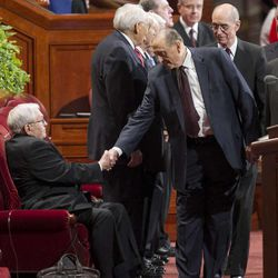 President Thomas S. Monson shakes hands with President Boyd K. Packer as he and his Counselors Henry B. Eyring and Dieter F. Uchtdorf walk onto the stand prior to the start of the morning session of 183 annual General Conference of the Church of Jesus Christ of Latter Day Saints Saturday, April 6, 2013 inside the Conference Center.