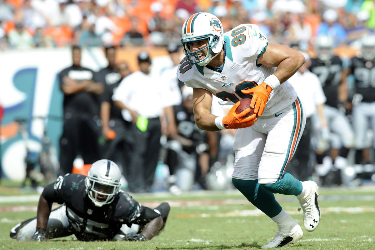 Miami Dolphins tight end Anthony Fasano (80) runs in for a touchdown as Oakland Raiders middle linebacker Rolando McClain (55) looks on