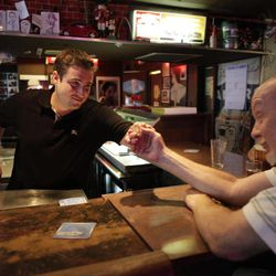 In this photo taken Aug. 16, 2012, Bar owner Frank Borst, left, gives a hand to patron Bob Wardsworth, 66, a Vietnam veteran originally from N.Y. at the King Eddy Saloon, one of the oldest and most colorful dive bars in Los Angeles. The King Eddy Saloon located near the Skid Row will close next September after more than 100 years as a bar, Prohibition-era speakeasy, post -Prohibition bar again, and home away home to Charles Bukowski, John Fante and numerous others.